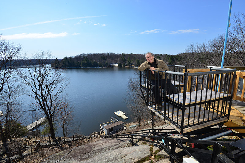 Cottage lifts elevation solutions owner on deck overlooking lake